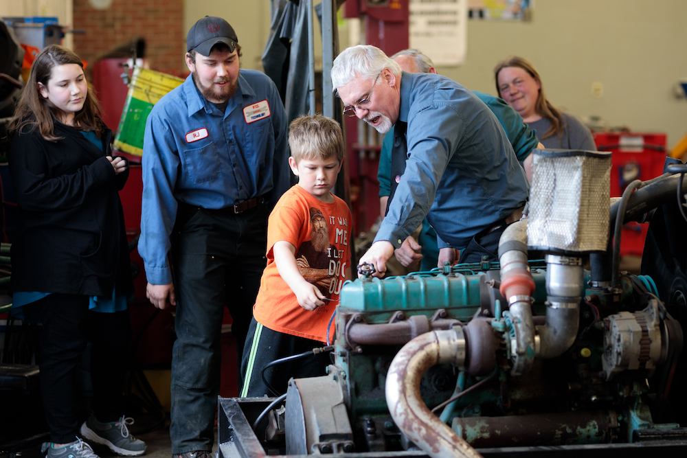 diesel instructor shows a young learner a diesel engine